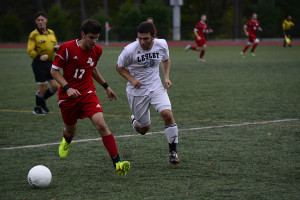 """Spencer Irwin, who was named a tri-captain for the upcoming 2015 season, shadows a Daniel Webster College player on October 18, 2014.  Courtesy of Lesley University Athletics."